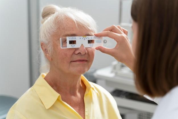 Пожилая женщина проверяет зрение в офтальмологической клинике