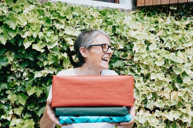 Старая женщина веселится и улыбается, получая подарки и подарки от своей дочери, концепция старшего, солнечный день