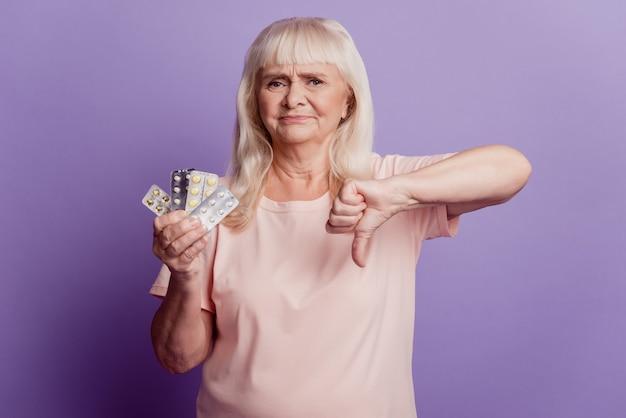 늙은 여자는 보라색 배경 위에 태블릿을 들고 엄지손가락을 아래로 표시합니다.