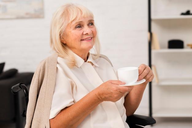 Старая женщина держит чашку чая