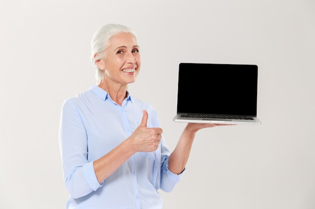 Old woman holding laptop and showing thumb up isolated
