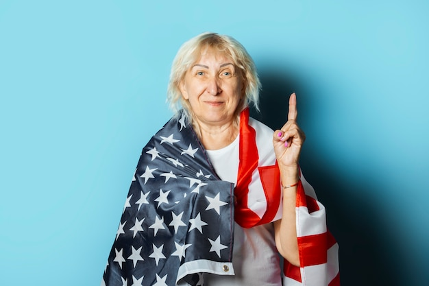 Old woman holds american flag on a blue background. independence day celebration concept, memorial day, emigration, us flag
