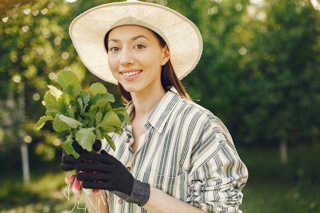 新鮮な大根を保持している帽子の老婆