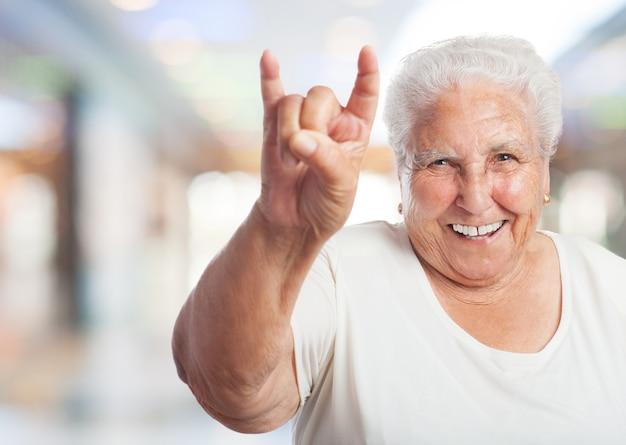 Старая женщина в торговом центре делают рога