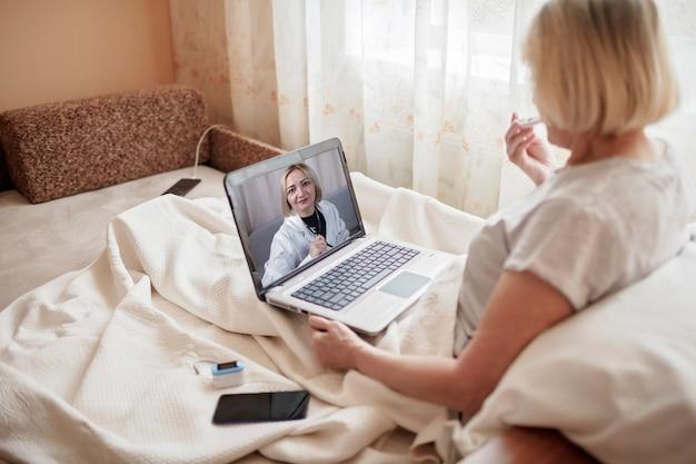 ラップトップの画面を見て、自宅でオンラインで医師に相談しているベッドの老婆、封鎖中の遠隔医療サービス、遠隔ビデオ通話、最新のハイテクヘルスケアアプリケーション