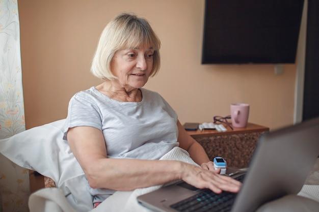 ノートパソコンの画面を見て、自宅でオンラインで医師に相談しているベッドの老婆、遠隔医療
