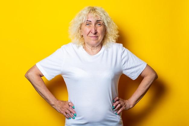 Старая женщина в повседневной белой футболке на желтой стене.