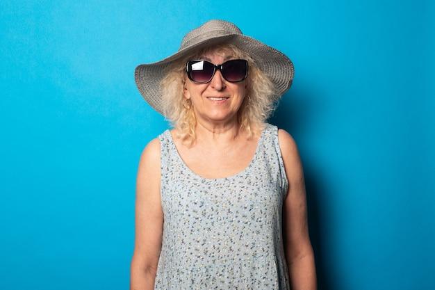 Старая женщина в платье и шляпе с очками