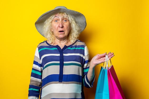 黄色の背景で購入した買い物袋を保持している帽子の老婆。