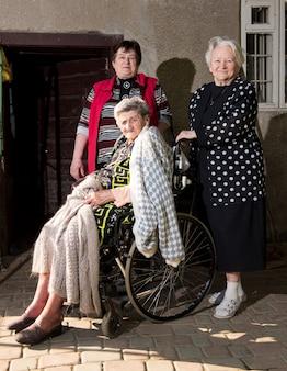 屋外で娘と妹と車椅子の老婆