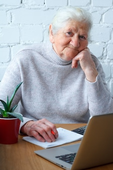 An old woman is sitting at the table in front of laptop.