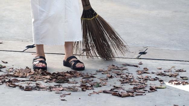 늙은 여자는 큰 긴 빗자루로 야외 시멘트 바닥에 마른 잎을 쓸고 있습니다.