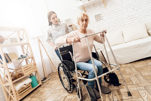 Old woman is trying to stand up from wheelchair.