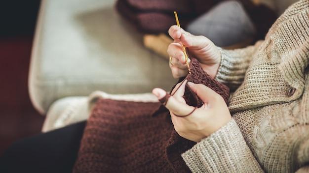 茶色のスカーフを編む老婆