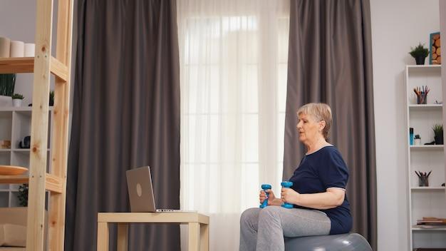 ラップトップでトレーニングレッスンを見て安定ボールに座ってダンベルを持ち上げる老婆。オンライントレーニング学習技術老婆リフティングトレーニング健康的なライフスタイルスポーツフィットネストレーニング自宅で