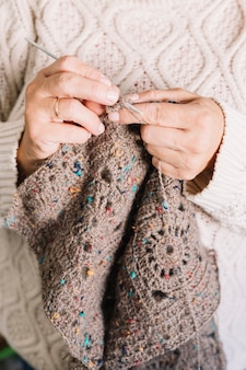 Old woman in light sweater knitting scarf