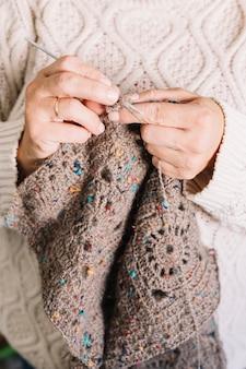 Anziana in maglione leggero che lavora a maglia sciarpa
