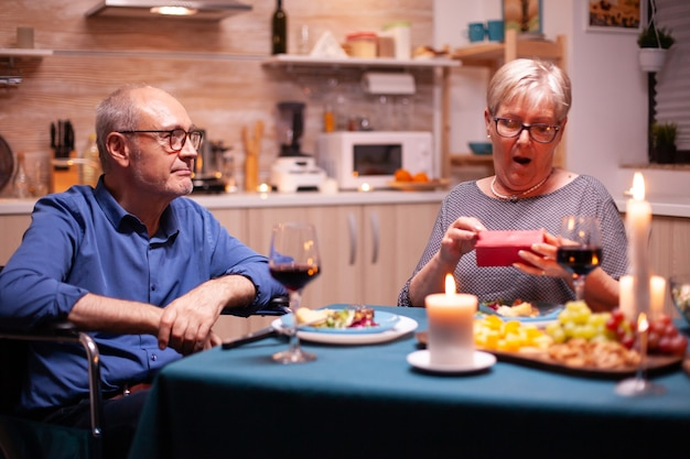 Old woman looking surprised holding gift from husband in wheelchair during festive dinner. happy cheerful elderly couple dining together at home, enjoying the meal, celebrating their marriage ,