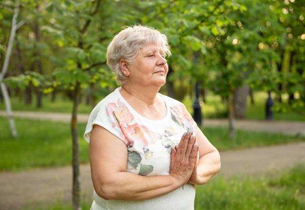 老婆の瞑想。自然の中でリラックスできる成熟した女性。年配の女性は公園でヨガをやっています。