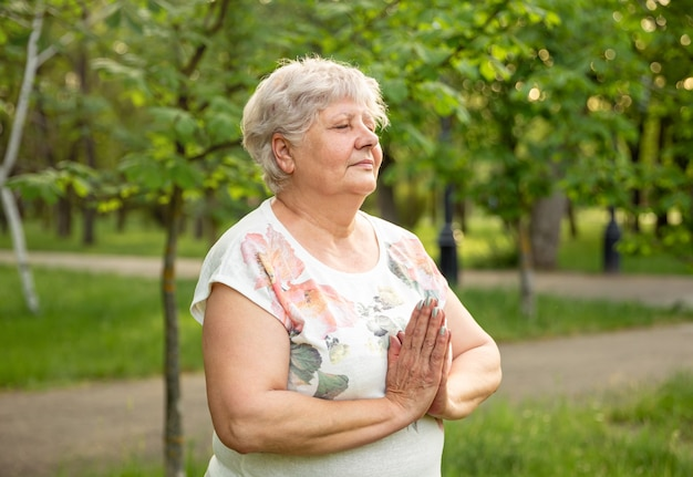 Old woman meditating. mature woman relaxing in nature. senior woman is doing yoga in the park.