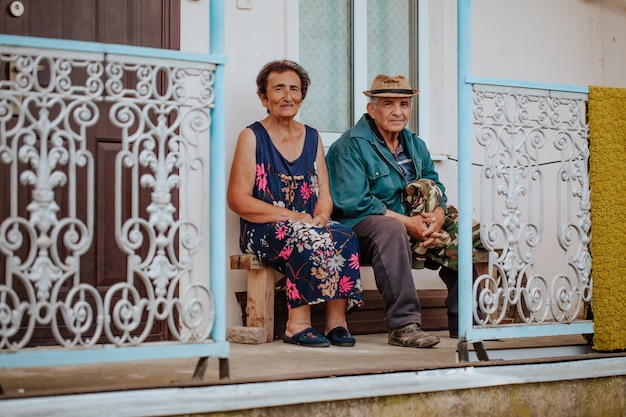 An old woman and an old man in a hat sit on a porch with a wrought iron railing