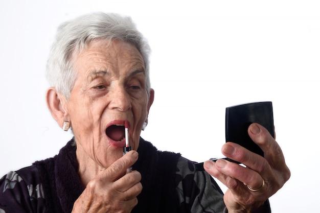 歳の女性が白い背景の上に彼女の唇を塗る