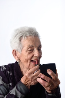Old woman painting her lips on white background