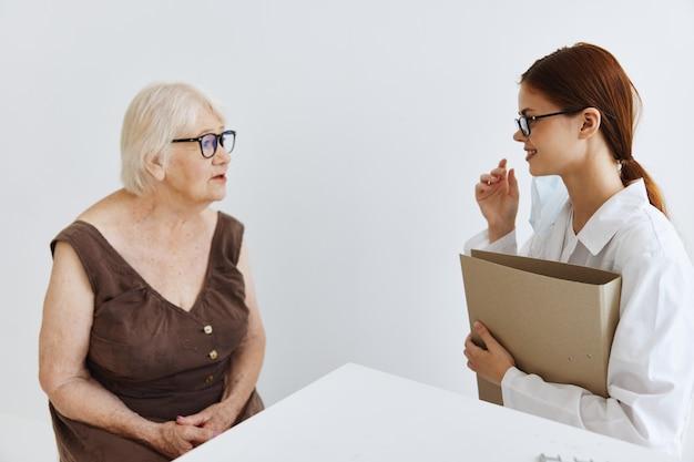 Осмотр пациента пожилой женщины врачом здравоохранения