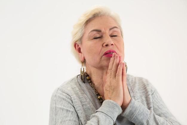 目を閉じて孤立した年配の女性を祈る老婆はあなたの心を浄化します