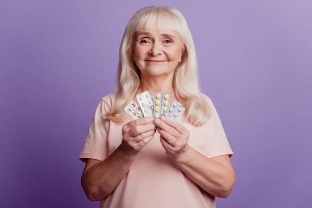 늙은 여자는 보라색 배경 위에 효과적인 의료 제품 정제를 제시합니다.