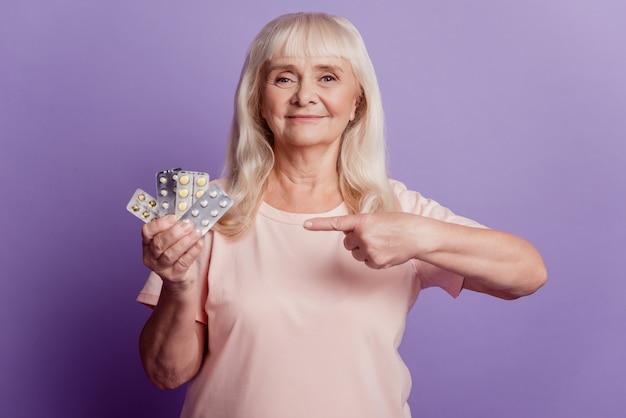 늙은 여자는 보라색 배경 위에 손가락으로 효과적인 의료 제품 정제를 제시합니다.
