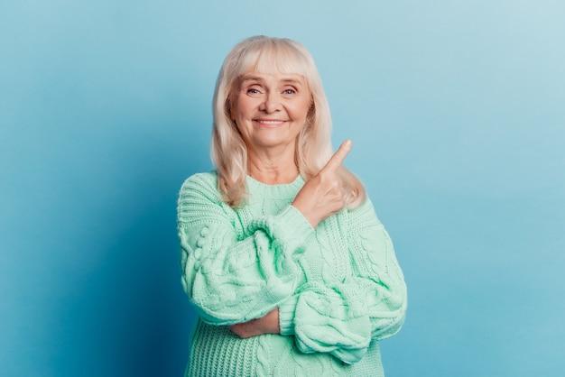파란색 배경에 고립 된 늙은 여자 발기인 포인트 손가락 빈 공간