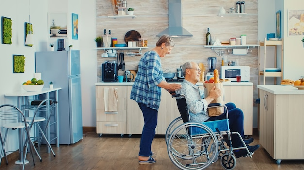 Old woman pushing invalid senior husband in wheelchair after arriving with grocery paper bag from supermarket. mature people with fresh vegetables for cooking breakfast.