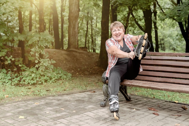 An old woman puts on roller skates and laughs while sitting on a park bench