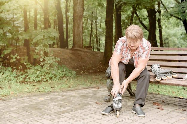 Old woman puts on roller skates while sitting on a park bench