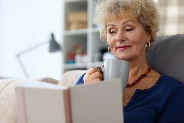 늙은 여자 읽기 책과 음료 허브 차 agailnst