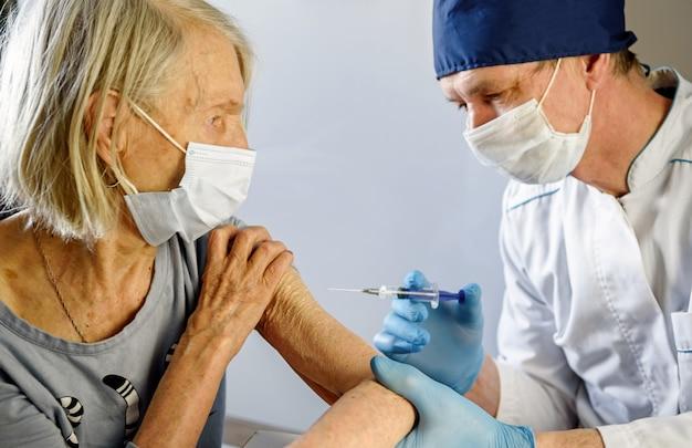 Пожилая женщина получает вакцину от covid-19 от врача.