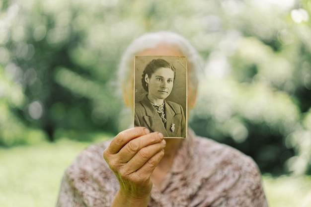 Old woman remembers her youth. grandma keeps her photo in her youth. memories. vintage old photos