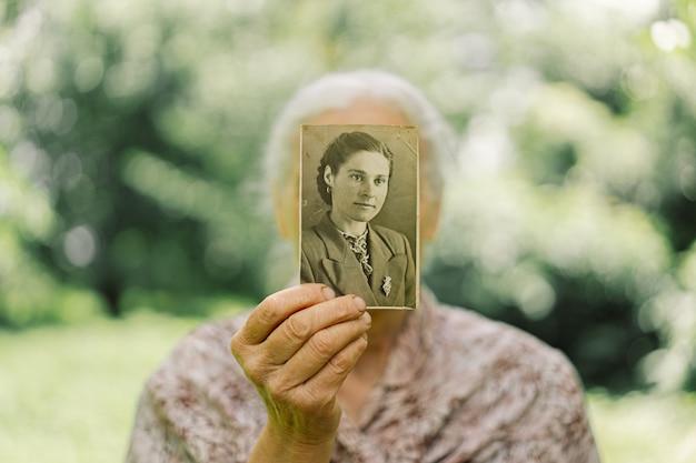 Старуха вспоминает молодость. бабушка хранит фото в молодости. воспоминания. винтаж старые фото