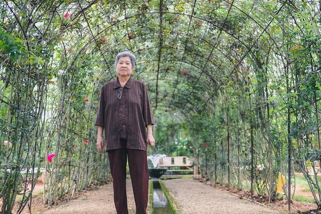 Пожилая женщина отдыхает в цветочном саду