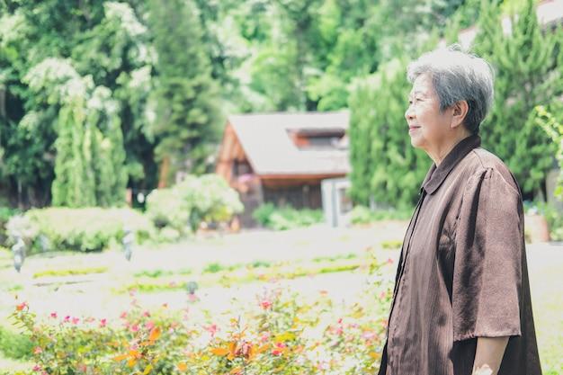 Старая женщина отдыхает в саду