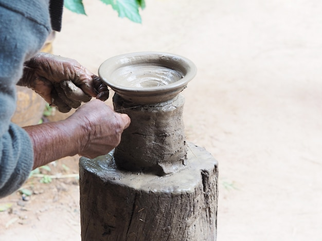 Old woman's hands sculpt clay pottery on wooden stand.