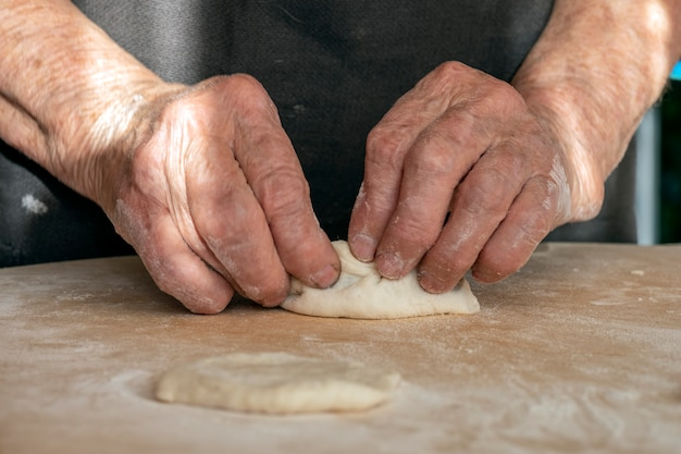 The old woman's overworked hands are making pies out of dough