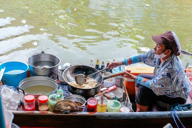 Старушка-продавец готовит омлет на лодке плавучий рынок ват тахиан в нонтхабури