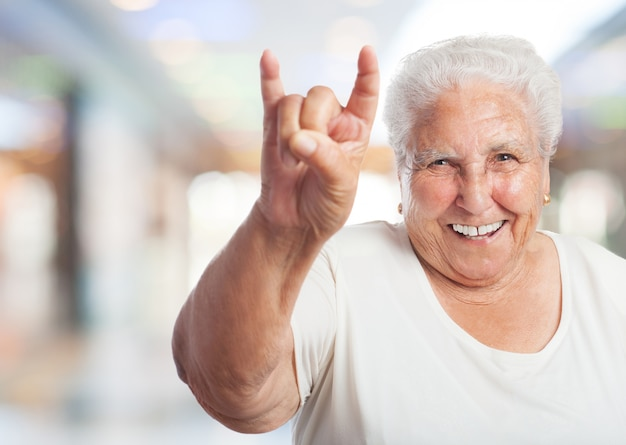 Old woman in a shopping center doing the horns