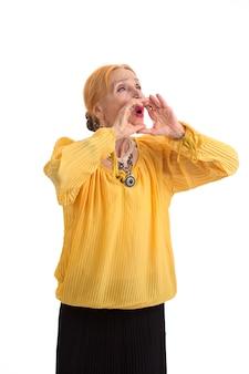 女性が口の近くで手を握って叫ぶ老婆は励まし、やる気を起こさせる