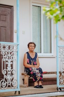 An old woman sit on a porch with a wrought iron railing
