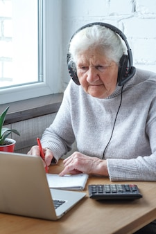 An old woman sits at a table in front of a laptop with headphones and writes into a notebook.