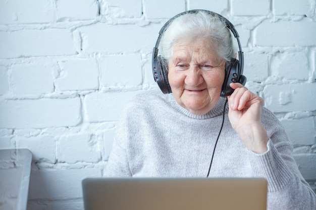 An old woman sits at a table in front of a laptop with headphones.
