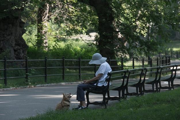 Старуха сидит в парке со своей маленькой собачкой